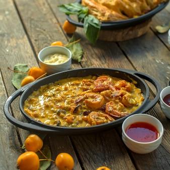 Vista lateral de ovos fritos com camarão e legumes em uma panela servida com molhos