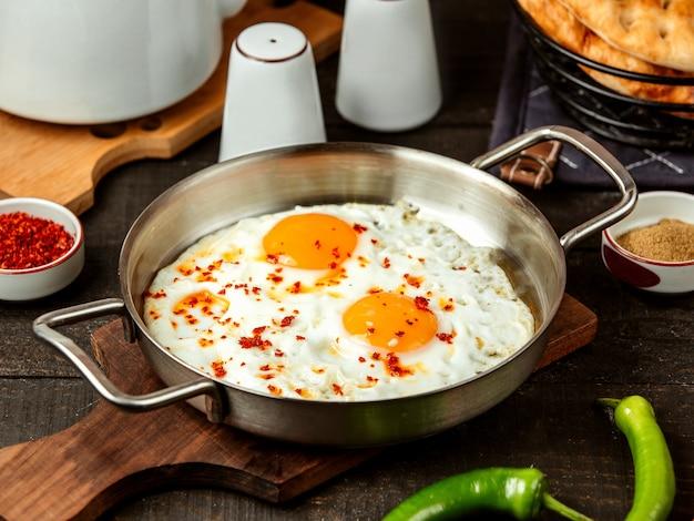 Vista lateral de ovos fritos com especiarias vermelhas em uma panela na placa de madeira
