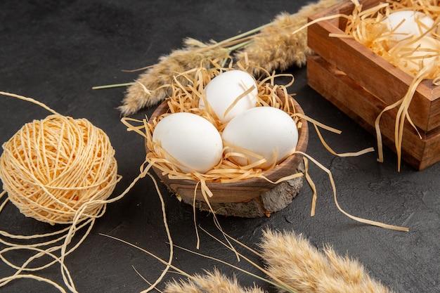 Vista lateral de ovos orgânicos em um espeto de corda de panela marrom em fundo escuro