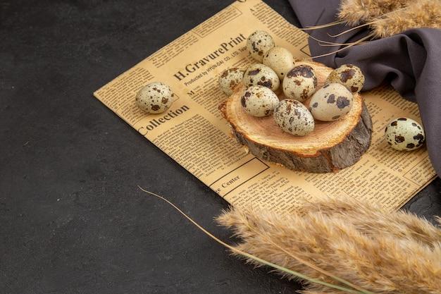 Vista lateral de ovos orgânicos em uma placa de madeira em um jornal velho espetado em uma toalha preta na superfície escura