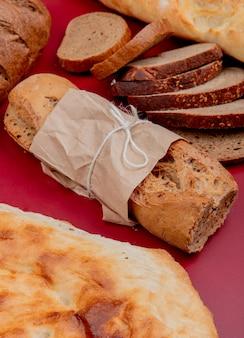 Vista lateral de pães como baguete crocante tandir preto fatiado pão de centeio na superfície do bordo