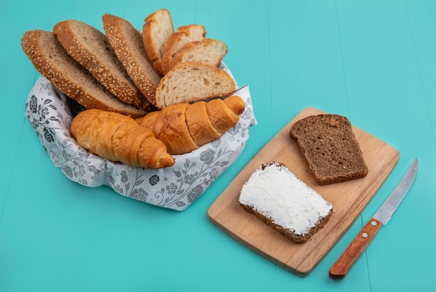 Vista lateral de pães como baguete de sabugo de sementes fatiadas e croissant em uma tigela e pão de centeio manchado com queijo em uma tábua de corte com uma faca no fundo azul