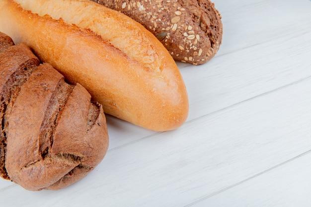 Vista lateral de pães como baguete de sementes vietnamita e preto e pão preto na mesa de madeira com espaço de cópia