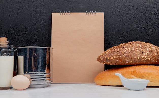 Vista lateral de pães como baguete preta e vietnamita semeada com copo de peneira de manteiga de ovo e bloco de notas na superfície branca e superfície preta com espaço de cópia