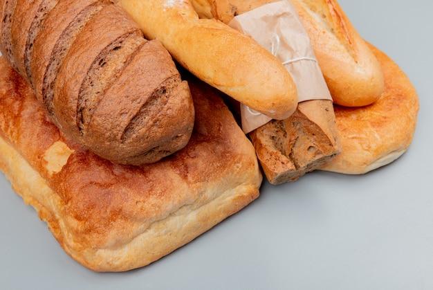 Vista lateral de pães como baguetes crocantes e vietnamitas caseiros pretos tandir na superfície azul