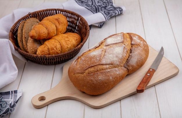 Vista lateral de pães como croissant e fatias de pão de espiga de milho sem sementes na cesta no pano e pão crocante com faca na tábua de corte no fundo de madeira