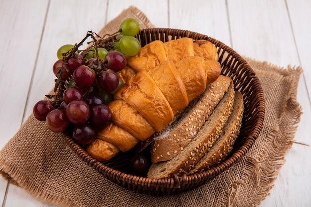 Vista lateral de pães como croissant e fatias de pão de sabugo integral com uva em uma cesta em saco no fundo de madeira