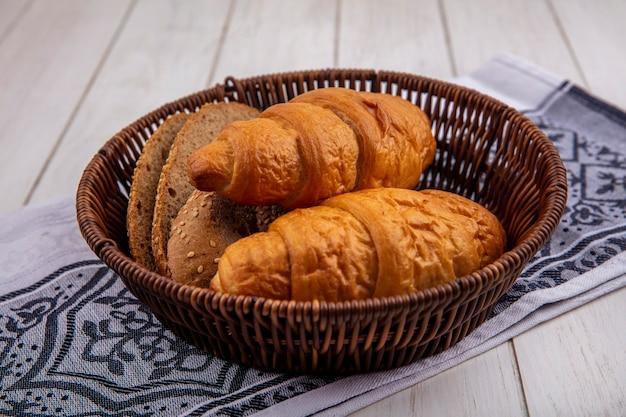 Vista lateral de pães como croissant e fatias de pão de sabugo marrom com sementes em uma cesta em um pano com fundo de madeira