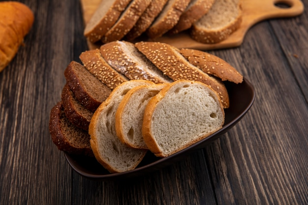 Vista lateral de pães como fatias de centeio-espiga marrom e outras brancas em uma tigela e na tábua de corte no fundo de madeira