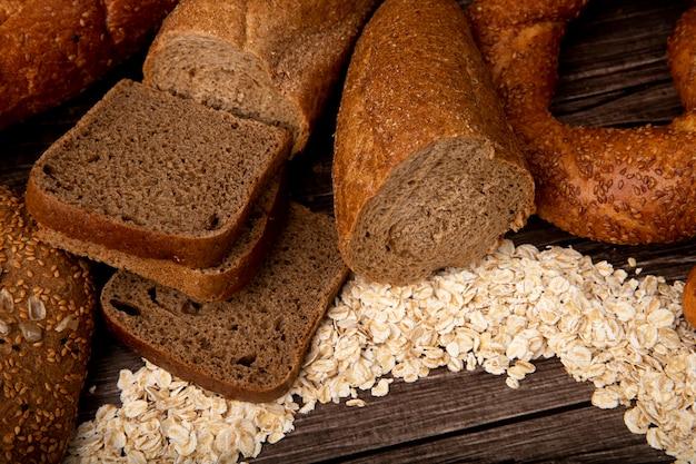 Vista lateral de pães como fatias de pão de centeio cortado em meia baguete bagel com flocos de aveia em fundo de madeira
