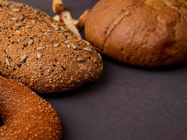 Vista lateral de pães como pão sanduíche de bagel e espiga clássica em fundo marrom com espaço de cópia