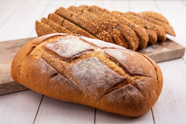 Vista lateral de pães em fatias de espiga de semente marrom na tábua e pão duro no fundo de madeira