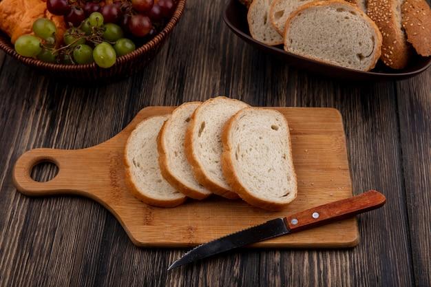 Vista lateral de pães em fatias de espiga marrom com sementes e brancas na tigela e na tábua com faca e cesta de uva para croissant no fundo de madeira