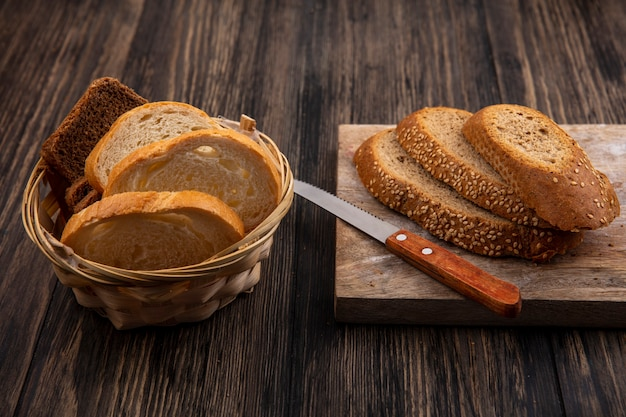 Vista lateral de pães fatiados espiga de semente marrom com faca na tábua e centeio branco na cesta no fundo de madeira