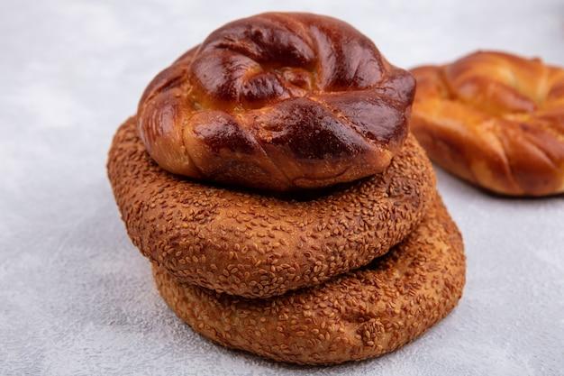 Vista lateral de pãezinhos deliciosos e macios com os tradicionais bagels turcos isolados em um fundo branco