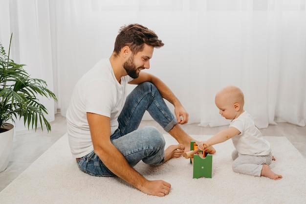 Vista lateral de pai e bebê brincando juntos em casa