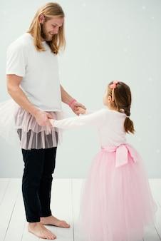 Vista lateral de pai e filha em saias tutu