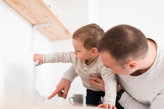 Vista lateral de pai e filho na cozinha
