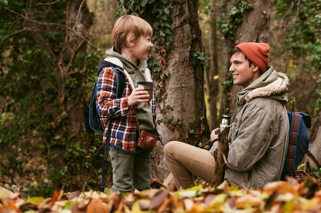 Vista lateral de pai e filho tomando chá quente ao ar livre na natureza