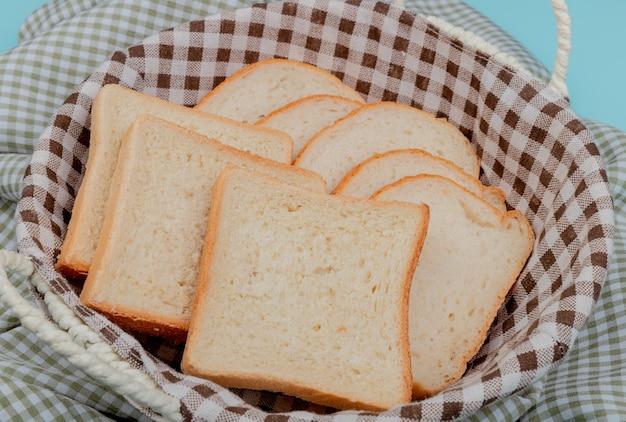 Vista lateral de pão branco fatiado na cesta no pano xadrez e azul