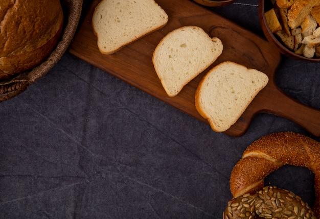 Vista lateral de pão branco fatiado na tábua com bagels e pedaços de pão no fundo marrom com espaço de cópia