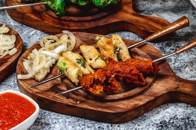 Vista lateral de pão de alho com carne picada verdes e cebola grelhada em uma placa