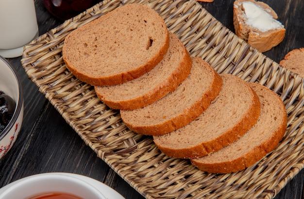 Vista lateral de pão de centeio fatiado no prato de cesta com azeite de oliva na mesa de madeira