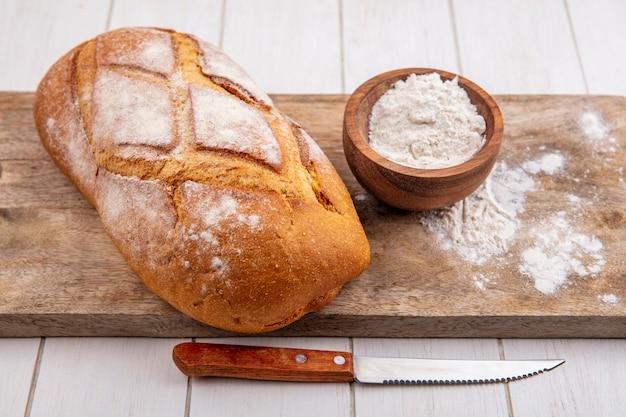 Vista lateral de pão de trigo caseiro com tigela de farinha na tábua e faca no fundo de madeira