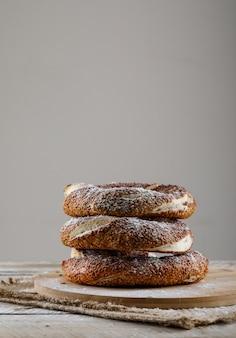 Vista lateral de pão turco em uma placa de corte e superfície de madeira, espaço para texto