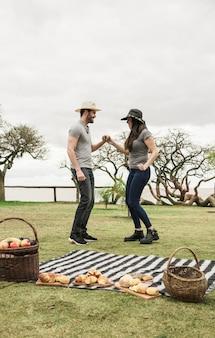 Vista lateral, de, par jovem, dançar, junto, em, piquenique, parque