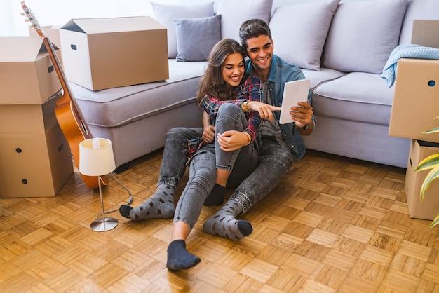 Vista lateral, de, par jovem, sentar chão, perto, caixa papelão, e, percorrendo, laptop moderno, enquanto, mudança, em, novo, apartamento, junto