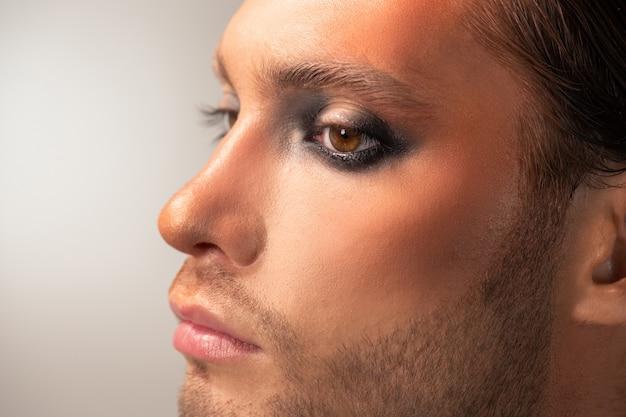 Vista lateral de parte do rosto de modelo masculino jovem sério com maquiagem de palco