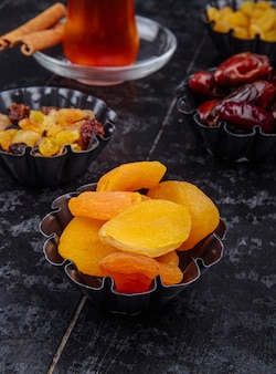 Vista lateral de passas de damascos secos e tâmaras secas em latas de mini torta servidas com chá em fundo preto