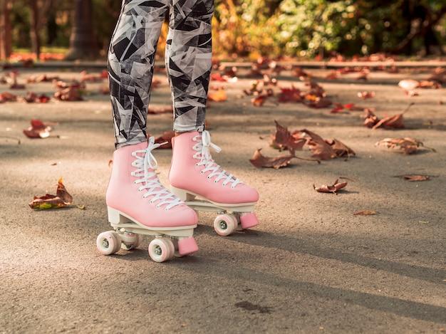 Vista lateral de patins na calçada com folhas