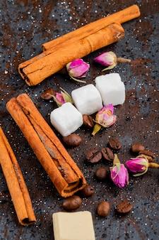 Vista lateral de paus de canela, cubos de açúcar e botões de rosa chá espalhados em fundo preto