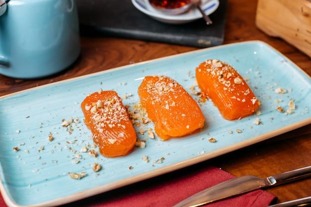 Vista lateral de pedaços de sobremesa turca de doces aromatizados com avelãs em cima da mesa