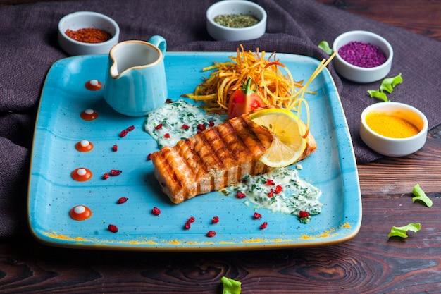 Vista lateral de peixe grelhado com guarnição, limão, molho e especiarias num prato azul sobre uma mesa de madeira escura horizontal