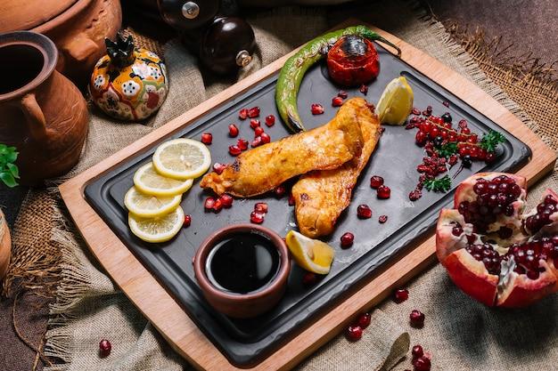 Vista lateral de peixe grelhado com tomate e pimenta grelhada com rodelas de limão e romã e molho narsharab