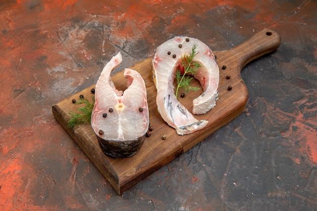 Vista lateral de peixes crus frescos e pimenta na tábua de madeira na superfície da mistura de cores