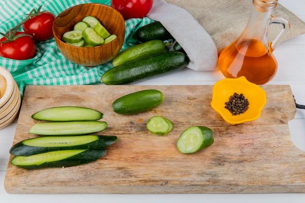 Vista lateral de pepinos inteiros fatiados e cortados e pimenta preta na tábua com tomates tigela de óleo derretido de fatias de pepino e pepinos derramando fora do saco na madeira