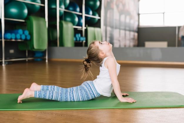 Vista lateral, de, pequeno, menina, prática, ioga, para, vida saudável