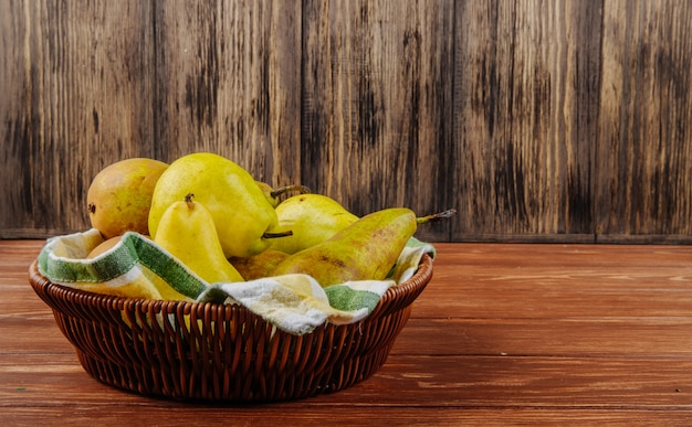 Vista lateral de peras maduras frescas em uma cesta de vime em um fundo de madeira