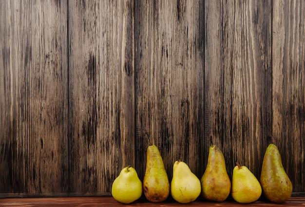 Vista lateral de peras maduras frescas em uma linha em um fundo de madeira com espaço de cópia