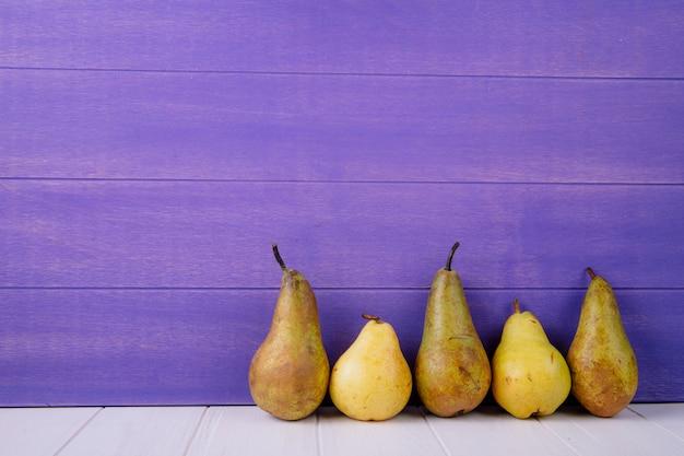 Vista lateral de peras maduras frescas no fundo de madeira roxo com espaço de cópia