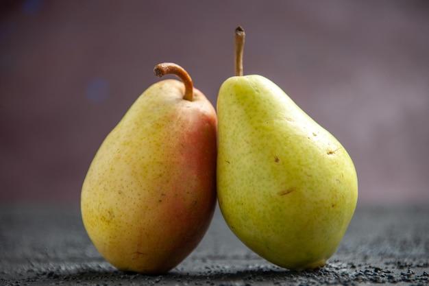 Vista lateral de peras na mesa duas peras verdes-amarelas-vermelhas maduras na mesa de madeira