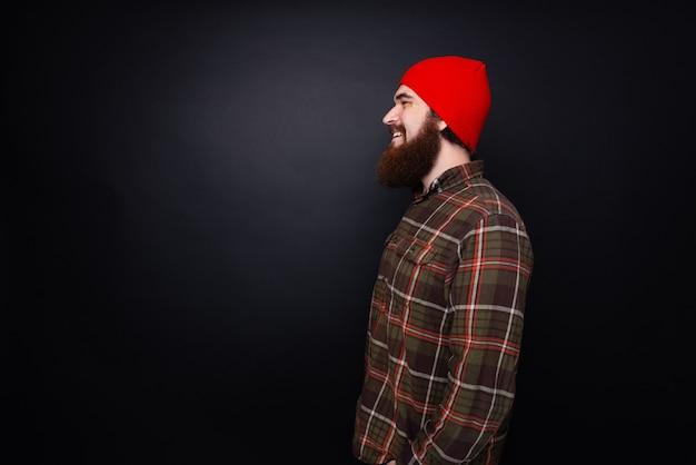Vista lateral de perfil de homem barbudo de chapéu vermelho
