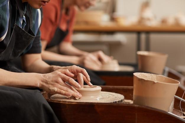 Vista lateral de perto de mãos femininas modelando argila na roda de oleiro na oficina, enquanto desfruta de artes e ofícios, copie o espaço