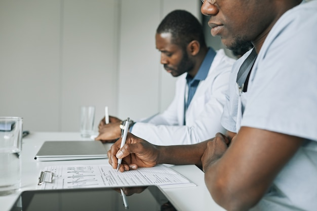 Vista lateral de perto de médicos afro-americanos fazendo anotações durante uma conferência médica, copie o espaço