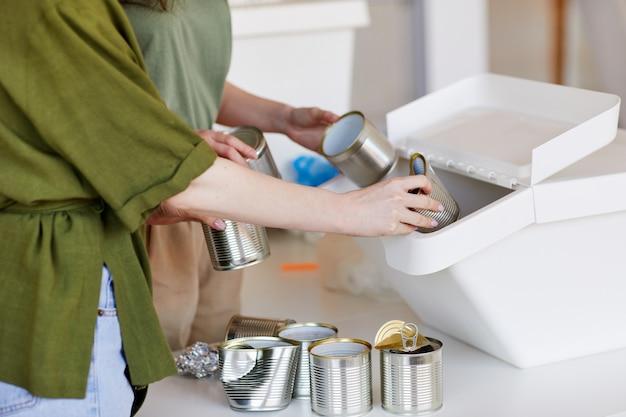 Vista lateral de perto de mulheres irreconhecíveis colocando latas de metal descartadas em um recipiente de plástico enquanto separam os resíduos para reciclagem
