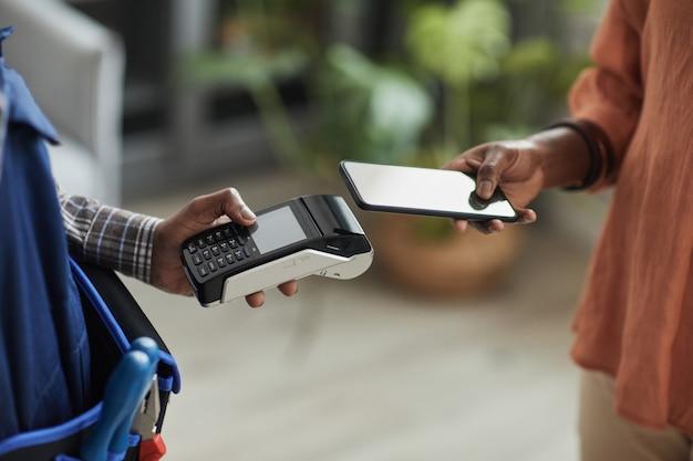 Vista lateral de perto de uma mulher irreconhecível pagando um trabalhador braçal por serviços passando o cartão no terminal do banco, copie o espaço